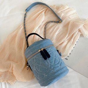 Baby blue denim bucket bag with chain crossbody.